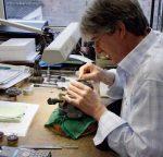 Auf einem Holzstock fixiert, bekommen Teile des Uhrwerks und des Gehäuses ihre Gravur. Den Schriftzug auf letzteren schneidet Jochen Benzinger frei Hand