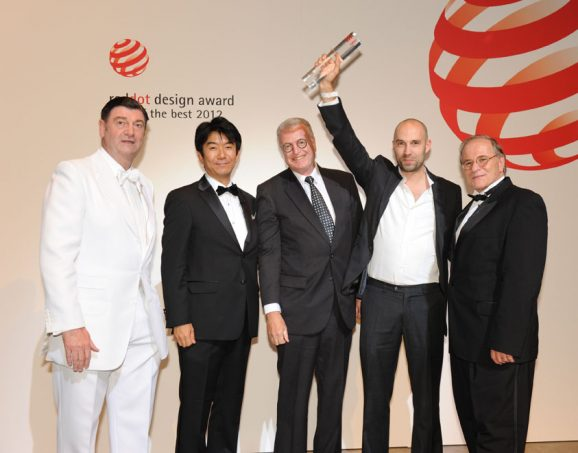 Überglücklich nehmen Simon Husslein (mit der Trophäe) und Pierre Nobs (links neben ihm) aus den Händen von Prof. Dr. Peter Zec, Initiator und CEO des Red Dot (ganz links), den begehrten Preis entgegen