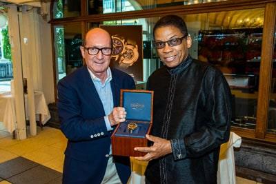 Bernard Fleury, CEO der Uhrenmarke Vulcain, überreicht dem Musiker Herbie Hancock die ihm gewidmete Armbanduhr