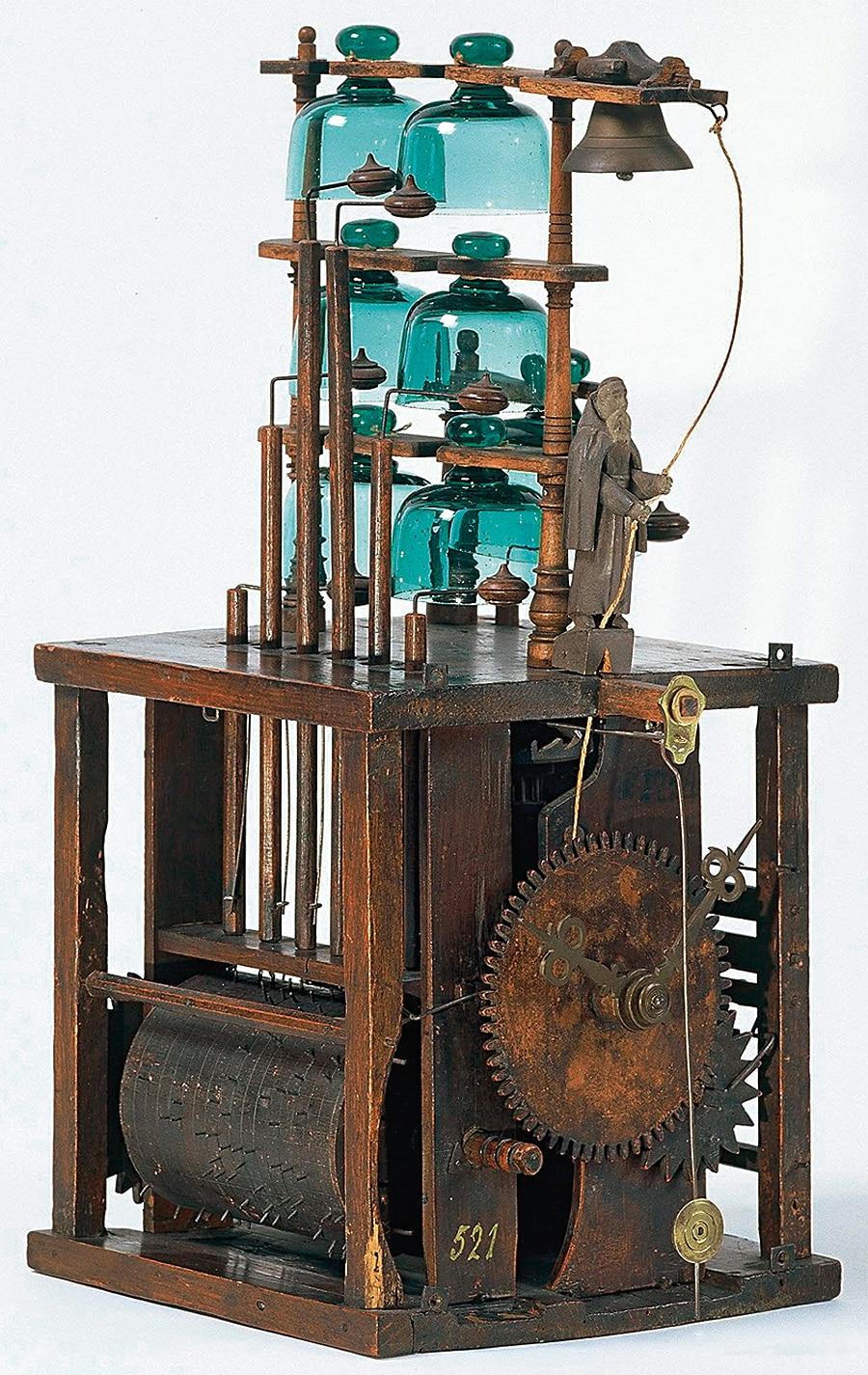 Frühe Musikuhr: Über ein Spielwerk mit Stiftenwalze werden die sechs Glasglocken angeschlagen. Die Mönchsfigur läutet zur Gebetszeit eine Metallglocke. Wohl von Johann Wehrle, Neukirch, um 1770