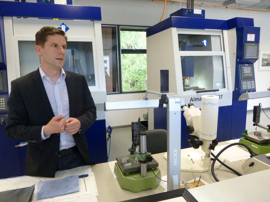 Konstrukteur Norbert Windegger erklärt die Einsatzmöglichkeiten der CNC-Maschinen im Hintergrund