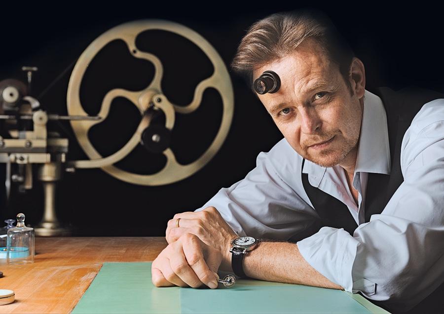 Peter Speake-Marin. Im Hintergrund ist das Rad einer alten Finissiermaschine zu sehen, ein typisches Designmerkmal seiner Uhr
