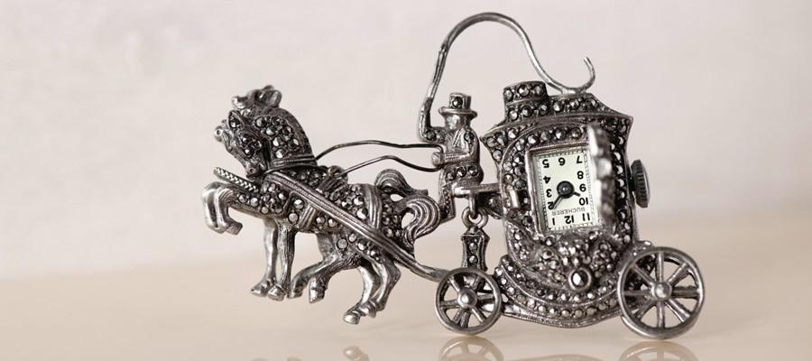 Die Pferdekutschen-Broschenuhr aus Silber ist mit Markasit besetzt.