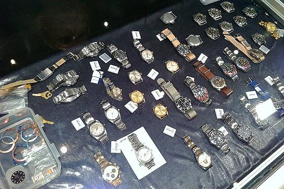 Vintage-Uhren und Zubehör auf dem Tisch eines Uhrenhändlers.