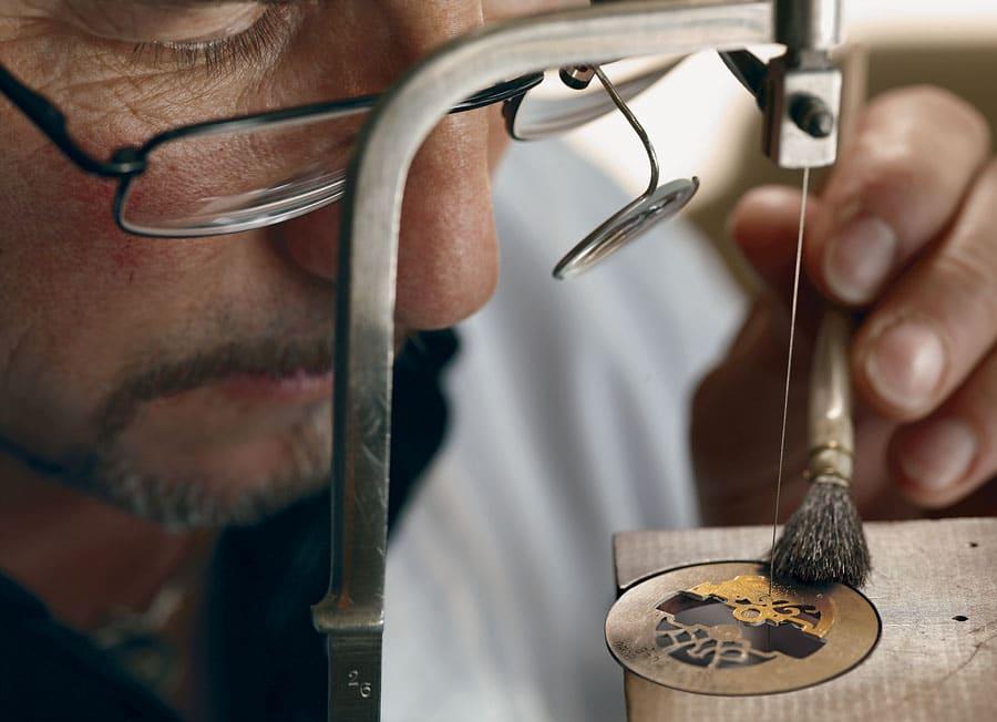 Laubsägearbeit: Der Skeletteur führt eine Säge durch das Metall des Uhrwerkteils.
