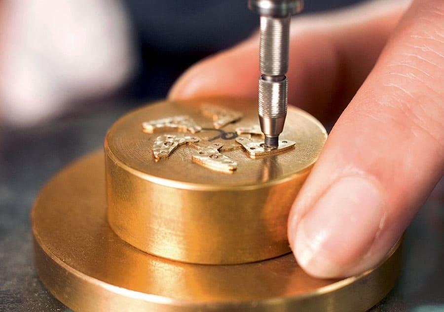 Beim Perlieren der Ankerkloben wird ein diamantgebundener, rotierender Gummistift von Hand kreisförmig über die Oberfläche der Werkteile bewegt.