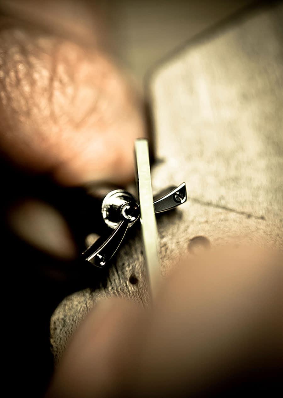 Mit einer feinen Feile wird die Komponente eines Uhrwerks angliert, also auf 45 Grad bei exakt gleichbleibender Breite abgeschrägt und poliert