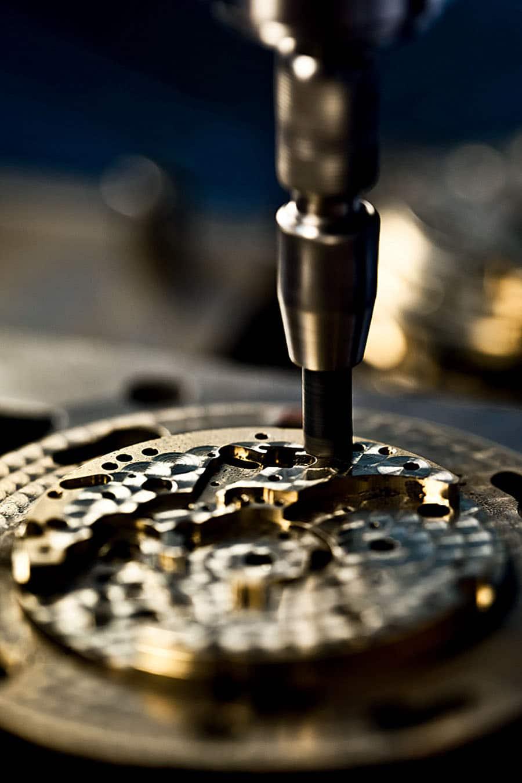 Ein kleiner Schleifkopf wird von Hand kurz auf ein Werkstück gedrückt, um es mit dicht beieinanderliegenden Kreisen, der Perlage, zu dekorieren