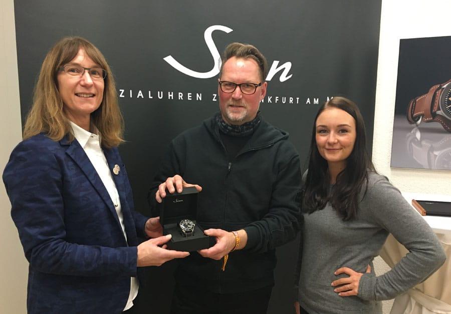 Arnd Dickel, Gewinner der MunichTime-Uhrenwahl, bekommt die EZM 9 TESTAF von Sabine Kleiter (links), Abteilung Marketing und Kommunikation Sinn Spezialuhren, und Melanie Feist (rechts), verantwortliche Online-Redakteurin Watchtime.net, überreicht