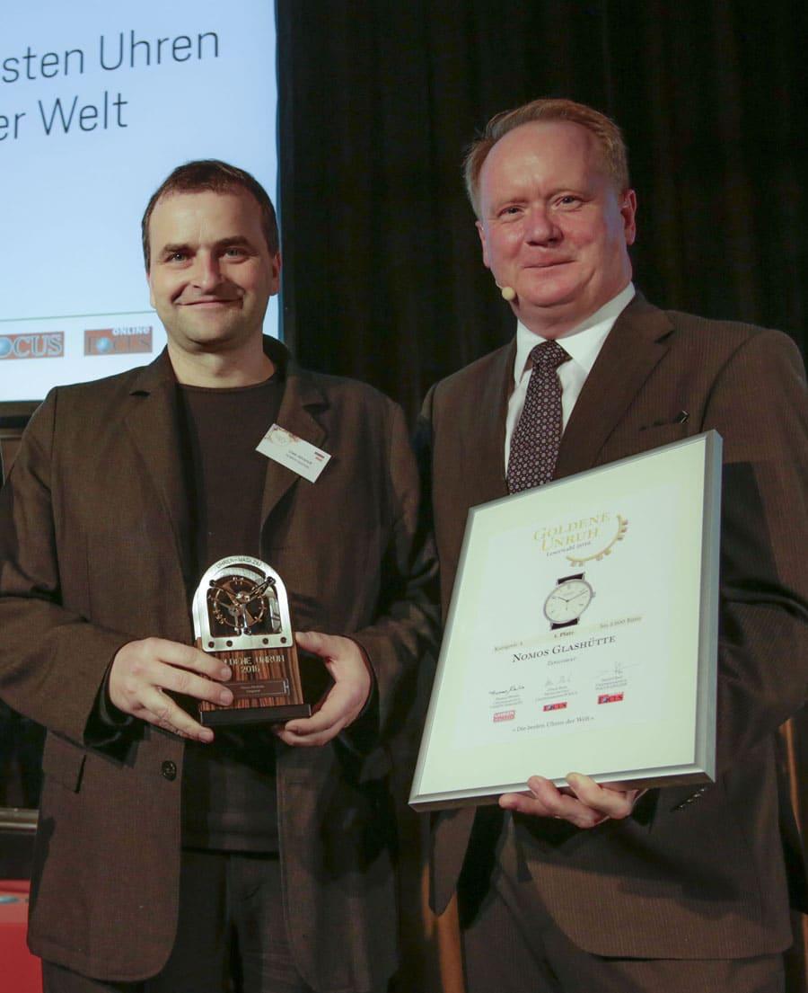 So sieht ein Gewinner aus: Uwe Ahrendt, CEO Nomos Glashütte (links), nimmt Urkunde und Trophäe von UHREN-MAGAZIN-Chefredakteur Thomas Wanka entgegen (Goldene Unruh 2016)