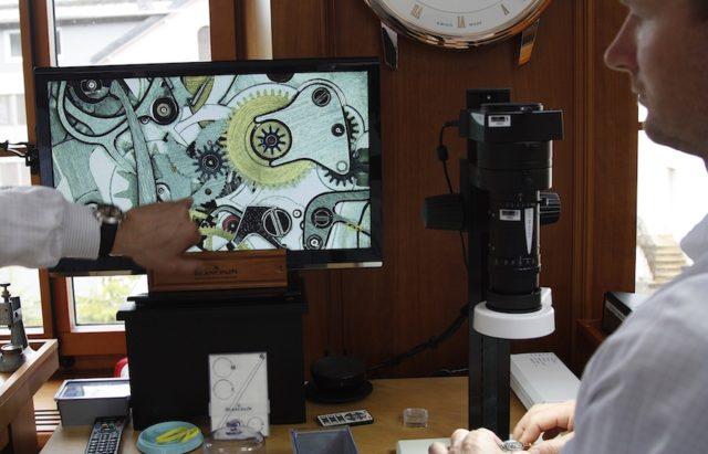 Die Funktionsweise einer Minutenrepetition veranschaulicht die Vergrößerung unter einem Mikroskop.