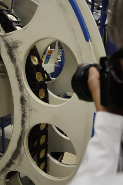 Verkettete Transportbehälter mit Platinenrohlingen werden zur automatisierten Weiterverarbeitung auf große Rollen gewickelt.