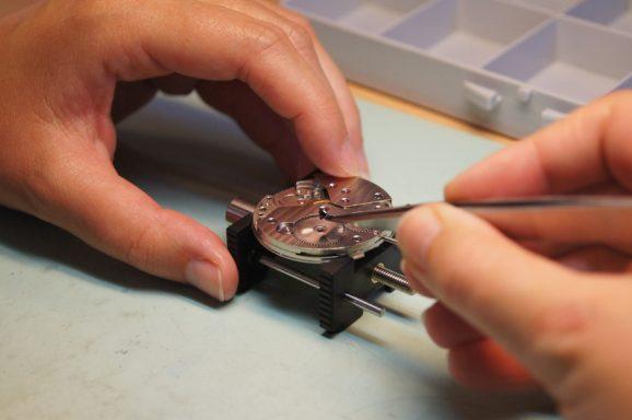 Schritt für Schritt wird das Uhrwerk auseinandergebaut. Hier zu sehen: Das Entfernen der Sperrradschraube.