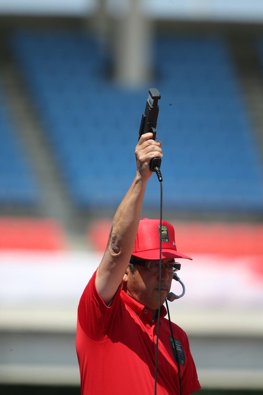 Die Startpistole gibt keinen Ton von sich. Der Knall wird elektronisch per Lautsprecher überall zeitgleich im Stadion verbreitet.