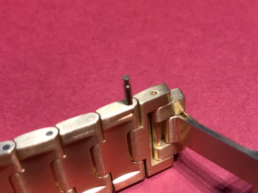 Ein Druck auf den Schlitz des Armands der Santos de Cartier setzt den Stift zum Ausbau des Gliedes frei.