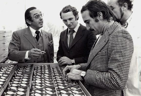 Jack Heuer (l.) erklärt den Rennsport-Assen Niki Lauda (2. v. l.) und Clay Regazzoni den Aufbau ihres goldenen Automatikchronographen.