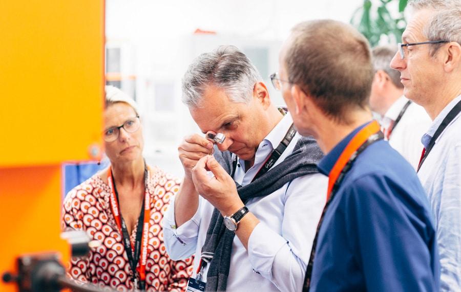 Mit dem Verfahren der Drahterodierung werden filigrane Teile aus einem Materialstreifen herausgearbeitet, wie die Teilnehmer der Leserreise durch die Lupe erkennen können.