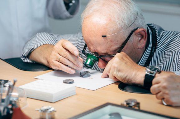 Die Gewichtsschrauben für die Schraubenunruh zählen mit einem Gewindedurchmesser von lediglich 0,35 mm zu den kleinsten in den Uhrwerken von Glashütte Original. Ein Teilnehmer der Leserreise nimmt diese genau in Augenschein.