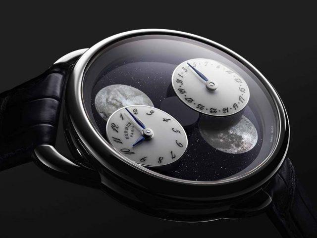 Zwei Scheiben mit Zeitanzeige und Datum kreisen um die Monde: Hermès Arceau l'heure de la lune, hier mit Zifferblatt aus Aventurin.