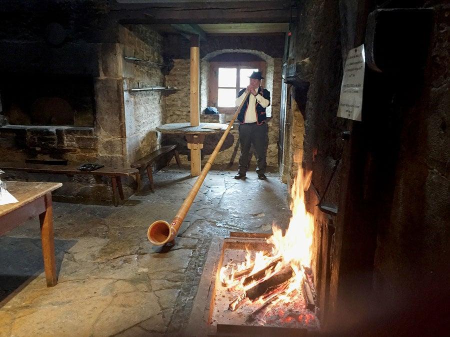 Chronos-Leserreise Jura 2019: Breitling begrüßt in einem alten Bauernhaus mit einem Alphornbläser