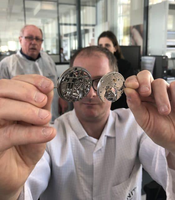 Chronos-Leserreise Jura 2019: Ein Zenith-Uhrmacher zeigt zwei Versionen des Zero-G-Kalibers mit kardanisch aufgehängter Hemmungaliber