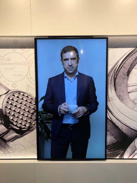 Der Besuch beginnt in der Ausstellung Manufacture Experience: Ein Mann mit Kaffeetasse erklärt in einer Multimedia-Installation den Entstehungsprozess einer Frederique-Constant-Uhr. Foto: HC