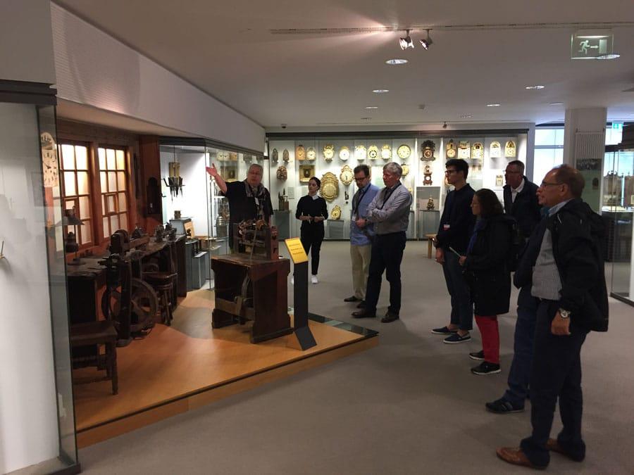 Die Teilnehmer der Leserreise vor einem historischen Uhrmacher-Arbeitsplatz